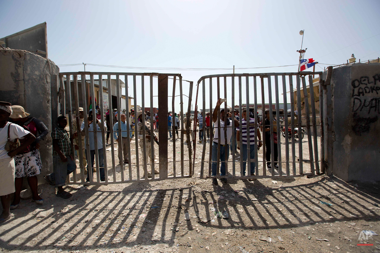 In this Aug. 4, 2015 photo, Dominican Republic soldiers and civilians stand at the gate that separates the D.R. from in Malpasse Haiti. After the D.R.'s June 17 deadline to apply for legal residency under a new program to organize the flow of migrants across the border from Haiti, more than 288,000 people applied. So far about 25,000 have received their documents while another 40,000 have been approved. The Dominican government says 66,000 people have returned to Haiti since the deadline. (AP Photo/Dieu Nalio Chery)