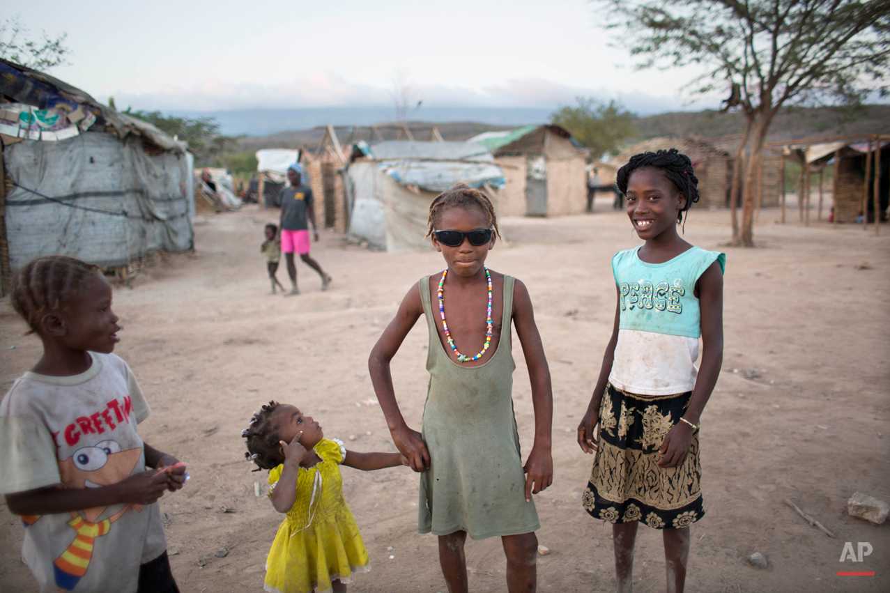 In this Aug. 3, 2015 photo, a Haitian girl wears her friend's sunglasses to pose for a photo in an encampment in Anse-a-Pitres, Haiti, where some Haitians are living after either fleeing from or getting deported from the Dominican Republic. Most of the children who were born in the D.R. have no birth certificates, according to their parents. (AP Photo/Dieu Nalio Chery)