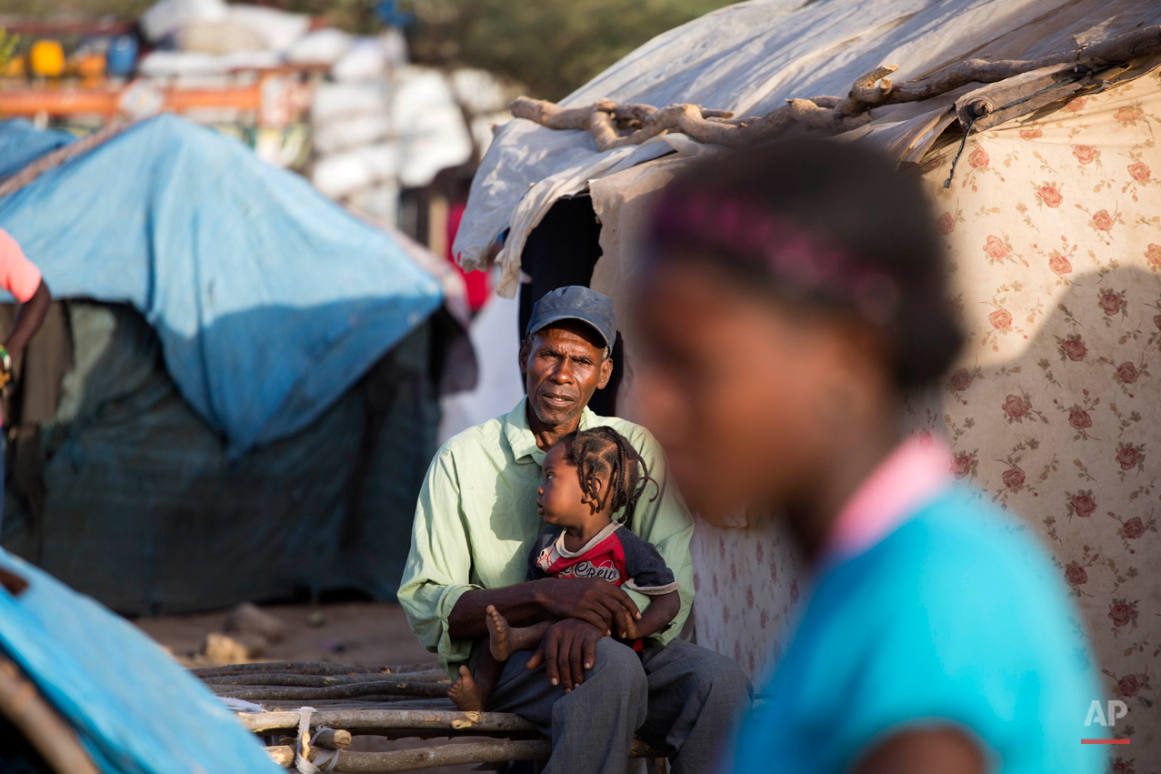 In this Aug. 4, 2015 photo, Haitian Elissene Jean Louis, 61, holds his 15-month-old son Geralson in the encampment where his family of six fled to by foot in Anse-a-Pitres, Haiti, on the border with the Dominican Republic. The camp, which lacks water, electricity or other services, is starting to resemble the settlements that emerged following the January 2010 earthquake, though they remain far smaller. (AP Photo/Dieu Nalio Chery)