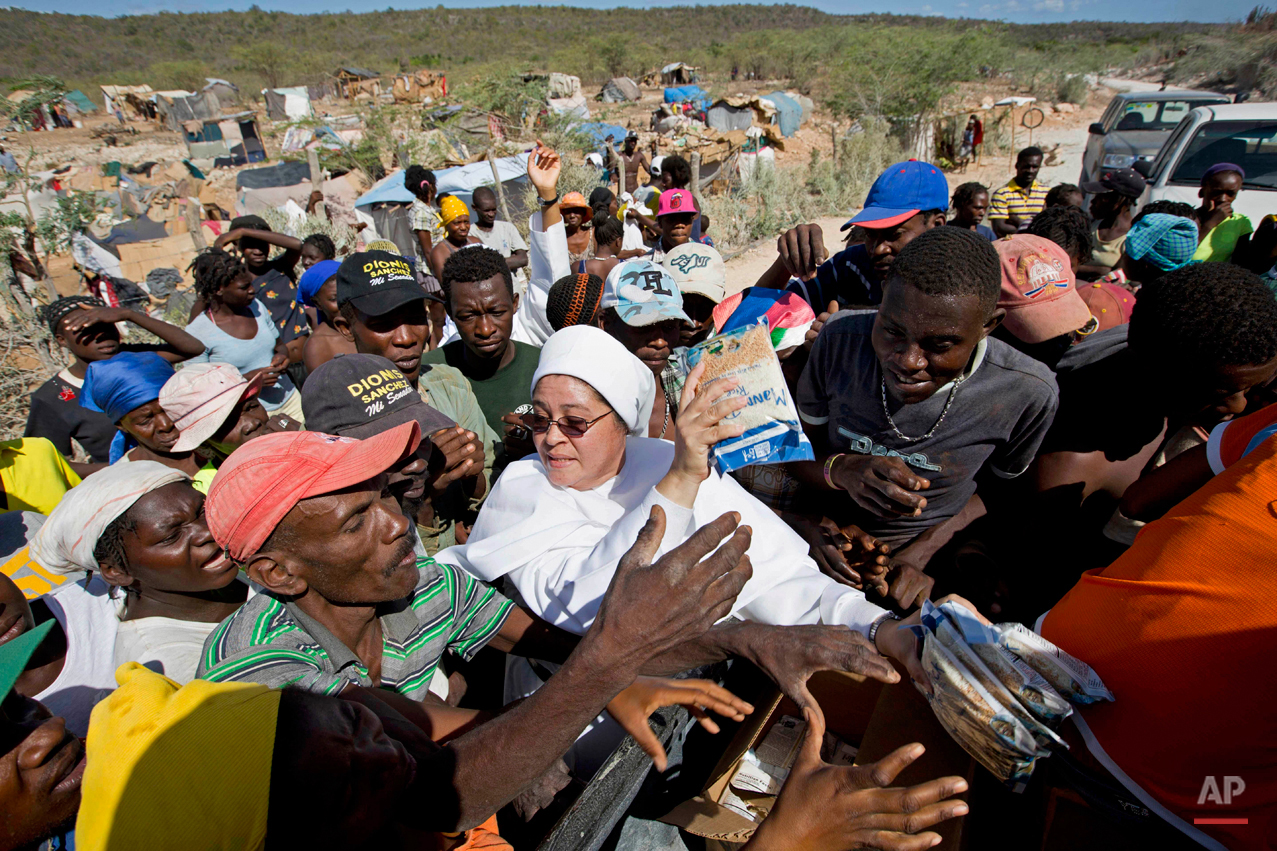 In this Aug. 3, 2015 photo, Sister Constencia of Fatima works to distribute rice, beans, oil and clothing to Haitians who were either deported or fled the Dominican Republic, at an encampment in Anse-a-Pitres, Haiti. The Haitian government has warned that the camps are becoming a crisis and has threatened to remove at least some of the people. However, some people in the camps, say they have nowhere else to go. (AP Photo/Dieu Nalio Chery)
