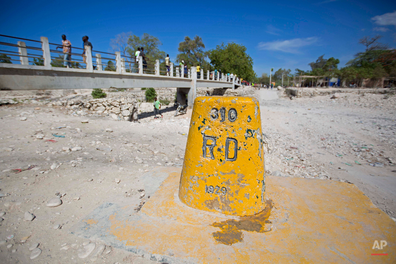 In this Aug. 3, 2015 photo, a post marks the border between Haiti and the Dominican Republic where a footbridge connects the Haitian town of Anse-a-Pitres, top, and the Dominican town of Perdernales. After the D.R.'s June 17 deadline to apply for legal residency under a new program to organize the flow of migrants across the border from Haiti, more than 288,000 people applied. So far about 25,000 have received their documents while another 40,000 have been approved. The Dominican government says 66,000 people have returned to Haiti since the deadline. (AP Photo/Dieu Nalio Chery)