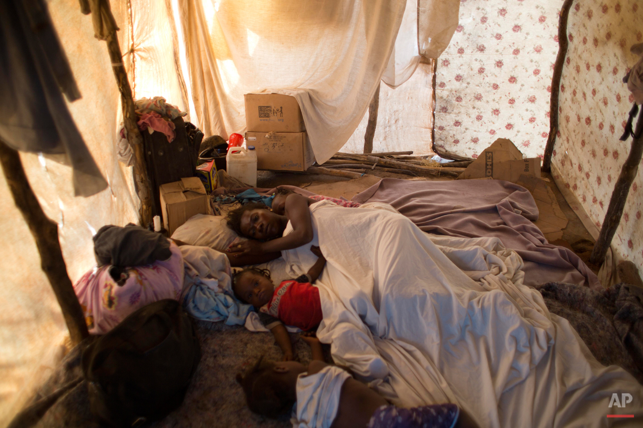 In this Aug. 3, 2015 photo, Haitian Molene Charles and her children sleep in their makeshift home in Anse-a-Pitres, Haiti, after fleeing by foot the the Dominican Republic. Charles, 28, said she had worked as a street vendor in the D.R. for 14 years but fled her home with her family of six after threats by locals. Her husband said he returned to find their home burned to the ground. (AP Photo/Dieu Nalio Chery)