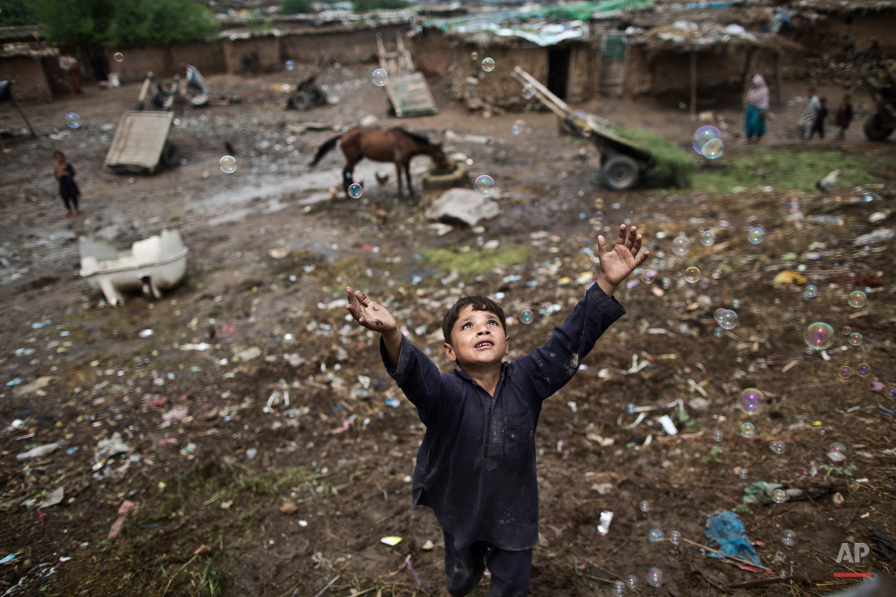 An Afghan refugee child chases bubbles released by other children, while playing on the outskirts of Islamabad, Pakistan, Friday, Aug. 8, 2014.  For more than three decades, Pakistan has been home to one of the worldís largest refugee communities: hundreds of thousands of Afghans who have fled the repeated wars and fighting in their country. (AP Photo/Muhammed Muheisen)