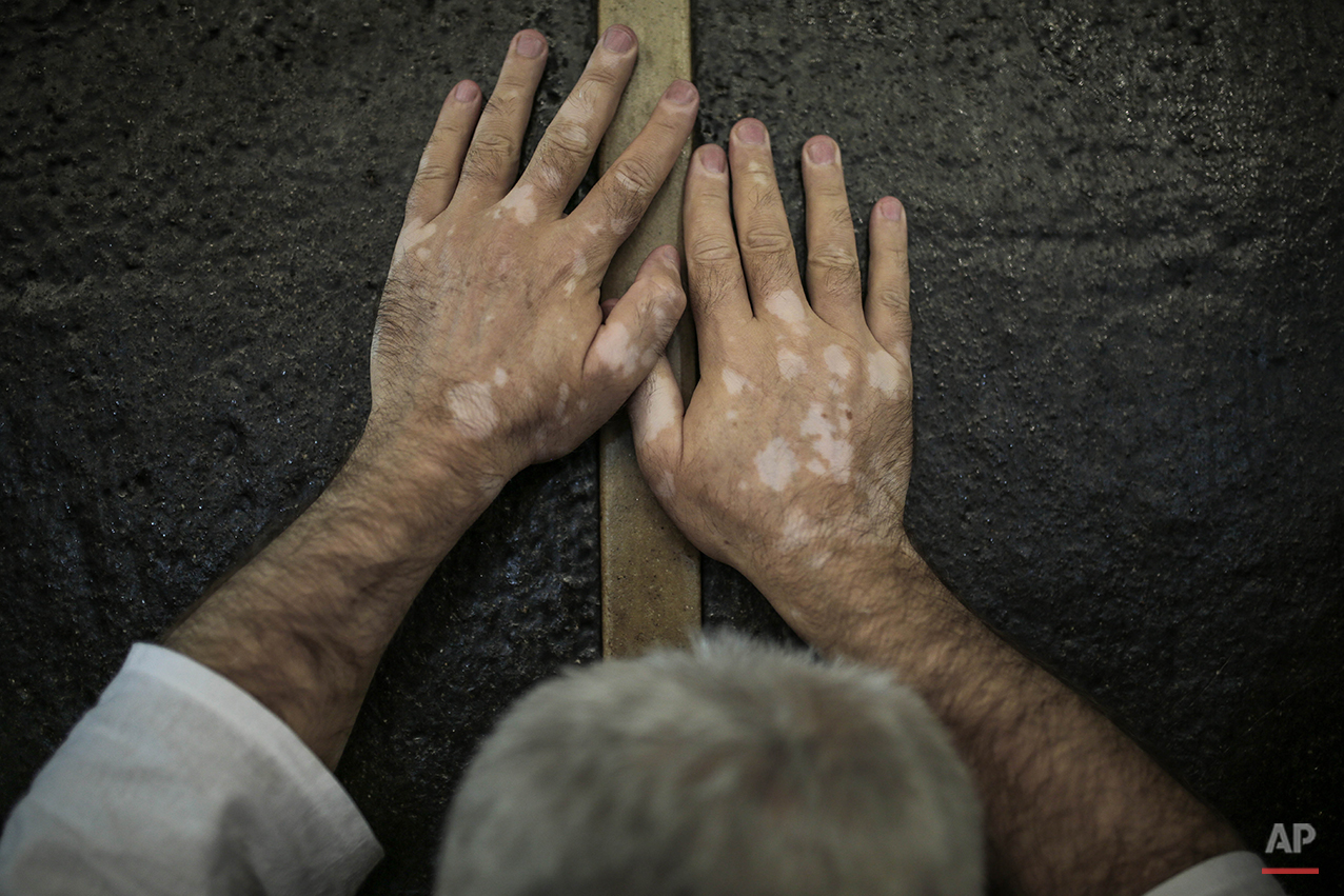 In this Monday, Sept. 21, 2015 photo, a Muslim pilgrim prays while touching the Kaaba, the cubic building at the Grand Mosque in the Muslim holy city of Mecca, while performing Tawaf, an anti-clockwise movement around the Kaaba and one of the main rites of the annual pilgrimage, known as hajj, in Saudi Arabia. (AP Photo/Mosa'ab Elshamy)