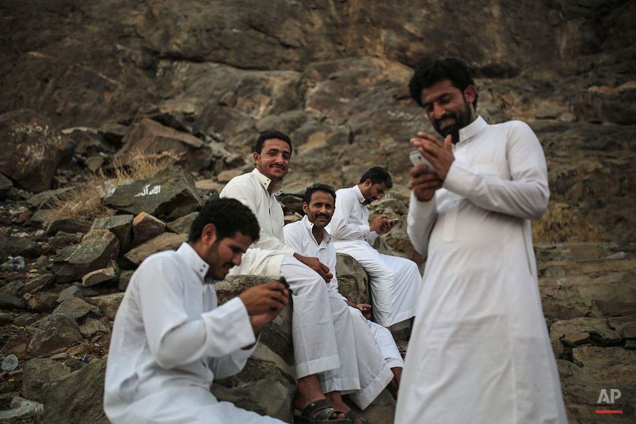 Muslim pilgrims rest while climbing the Noor Mountain to the Hiraa cave, where Prophet Muhammad received his first revelation from God to preach Islam, on the outskirts of Mecca, Saudi Arabia, Friday, Sept. 18, 2015. Hajj is expected to start on Monday. More than 1 million pilgrims have already arrived for the annual pilgrimage, which all able-bodied Muslims are required to perform once in their lives. (AP Photo/Mosa'ab Elshamy)