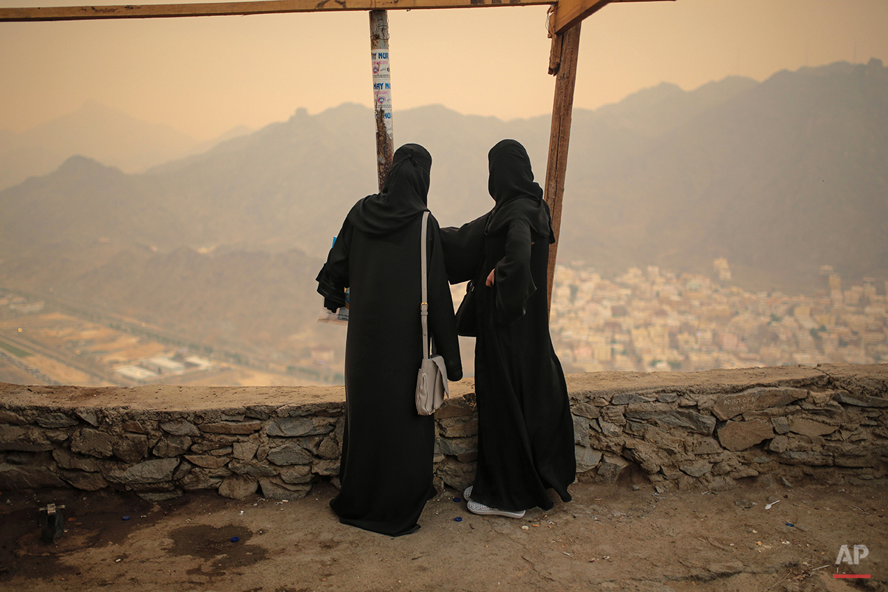 Muslim pilgrims observe a general view of the holy city of Mecca atop the Noor Mountain outside the Hiraa cave, where Prophet Muhammad received his first revelation from God to preach Islam, on the outskirts of Mecca, Saudi Arabia, Friday, Sept. 18, 2015. Hajj is expected to start on Monday. More than 1 million pilgrims have already arrived for the annual pilgrimage, which all able-bodied Muslims are required to perform once in their lives.  (AP Photo/Mosa'ab Elshamy)