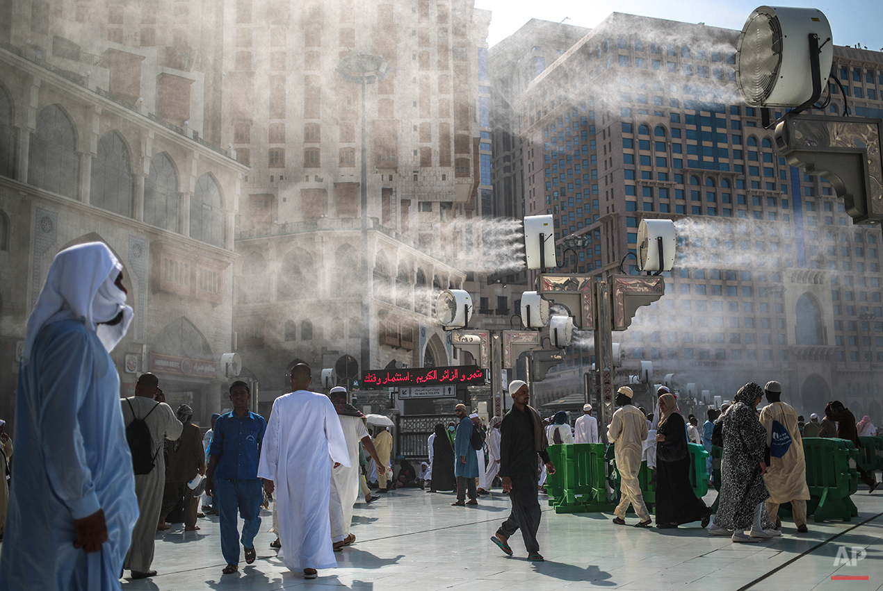 Water is sprayed over Muslim pilgrims to cool them down during the afternoon heat as they walk outside the Grand Mosque in the holy city of Mecca, Saudi Arabia, Tuesday, Sept. 15, 2015. Despite the crane accident on Friday, almost one million pilgrims have arrived as of Tuesday ahead of the hajj. (AP Photo/Mosa'ab Elshamy)