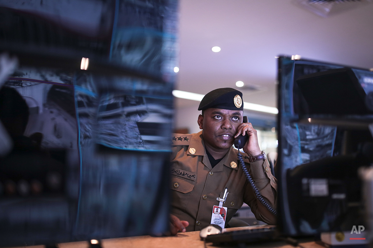 In this Saturday, Sept. 19, 2015 photo, a Saudi security officers monitors live feed screens showing Muslim pilgrims in the holy city of Mecca, along with highways and high density areas, a few days before the annual pilgrimage, known as the hajj, in Mecca, Saudi Arabia. Saudi Arabia has deployed 100,000 security personnel to oversee the annual Islamic hajj pilgrimage that begins on Tuesday, the Interior Ministry spokesman said, underscoring both the massive arrangements needed to secure one of the largest pilgrimages in the world and the multitude of threats the hajj faces. (AP Photo/Mosa'ab Elshamy)