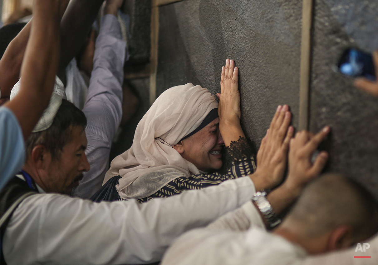 In this Monday, Sept. 21, 2015 photo, a Muslim pilgrim cries while praying at the Kaaba, the cubic building at the Grand Mosque in the Muslim holy city of Mecca, during the annual Pilgrimage, known as hajj, in Saudi Arabia. (AP Photo/Mosa'ab Elshamy)