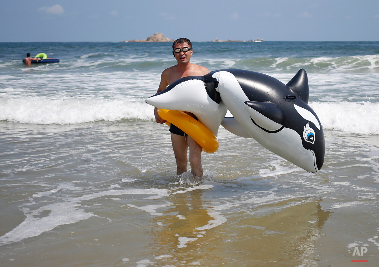 A man walks with an inflatable orca at Sijung Ho beach in North Korea, Tuesday, Aug. 18, 2015. The beach is a popular tourist destination for locals and foreigners alike. (AP Photo/Dita Alangkara)