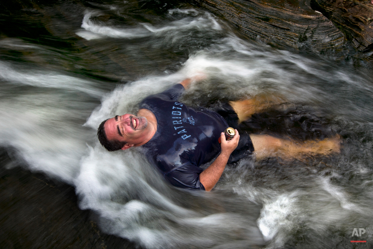 """Troy Munford soaks in the waters of Sunday River in Riley Township, Maine, Wednesday, Aug. 19, 2015. Munford, a tour and travel sales manager at the Sunday River Ski Resort, and many of his co-workers were enjoying an afternoon escape from work to beat the heat at the river. """"The whole office played hooky,"""" he said. (AP Photo/Robert F. Bukaty)"""