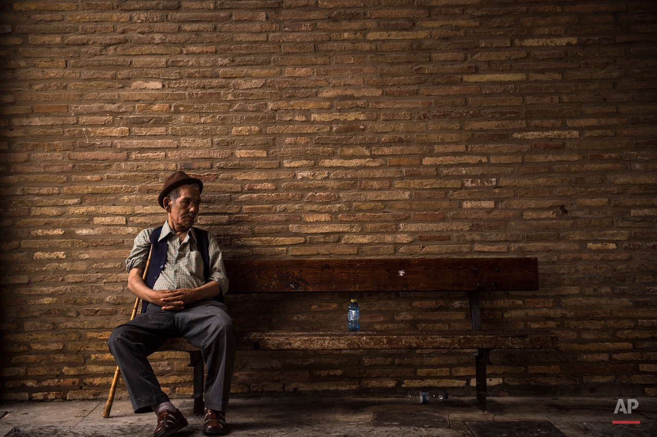 A man rests sitting on a bench next to a bottle of water, in the small village of Arguedas, northern Spain, Thursday, Aug. 6, 2015. (AP Photo/Alvaro Barrientos)