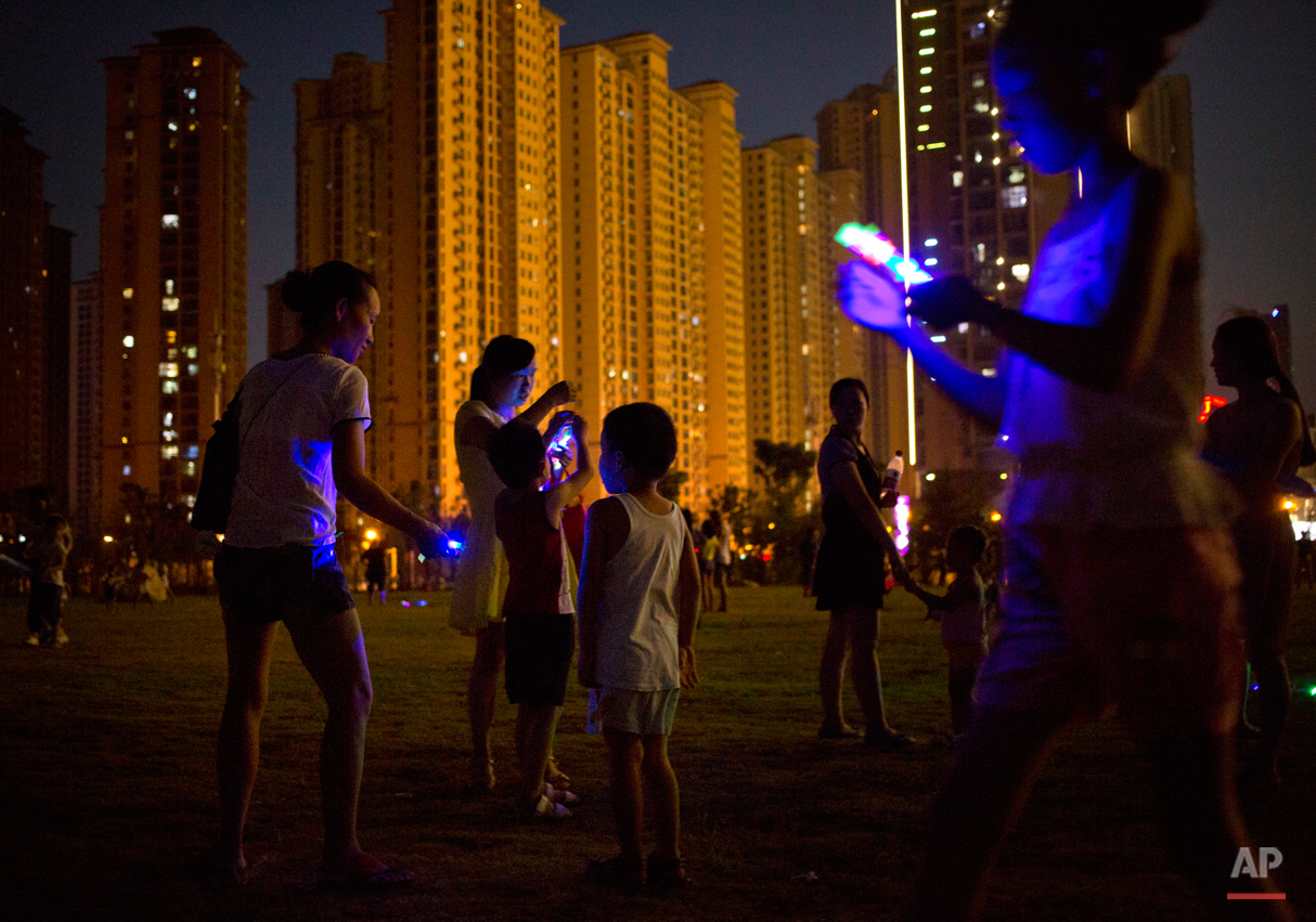 """People play with illuminated toys in a public park in Wuhan in central China's Hubei province Friday, Aug. 7, 2015. Wuhan is known in China as one of the """"Three Furnaces"""", cities notorious for their summer heat and humidity, and residents often wait until nightfall to take to the outdoors for outdoor activities. (AP Photo/Mark Schiefelbein)"""