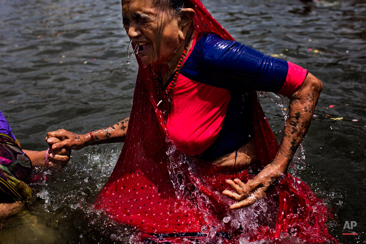 In this Wednesday, Aug. 26, 2015, photo, an elderly Hindu devotee performs a holy dip in the Godavari River during Kumbh Mela, or Pitcher Festival, in Nasik, India. Millions of Hindus are expected to immerse themselves in the Godavari River as a way to cleanse themselves of sin and come closer to God at this year's Kumbh Mela festival. (AP Photo/Bernat Armangue)