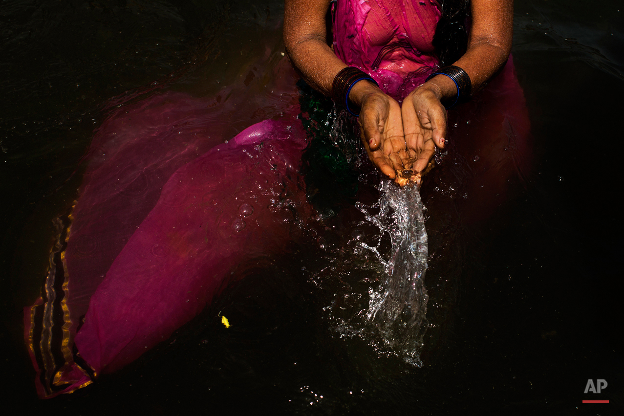 In this Wednesday, Aug. 26, 2015, photo, a Hindu devotee performs a ritual in the Godavari River during Kumbh Mela, or Pitcher Festival, in Nasik, India. Millions of Hindus are expected to immerse themselves in the Godavari River as a way to cleanse themselves of sin and come closer to God at this year's Kumbh Mela festival. (AP Photo/Bernat Armangue)