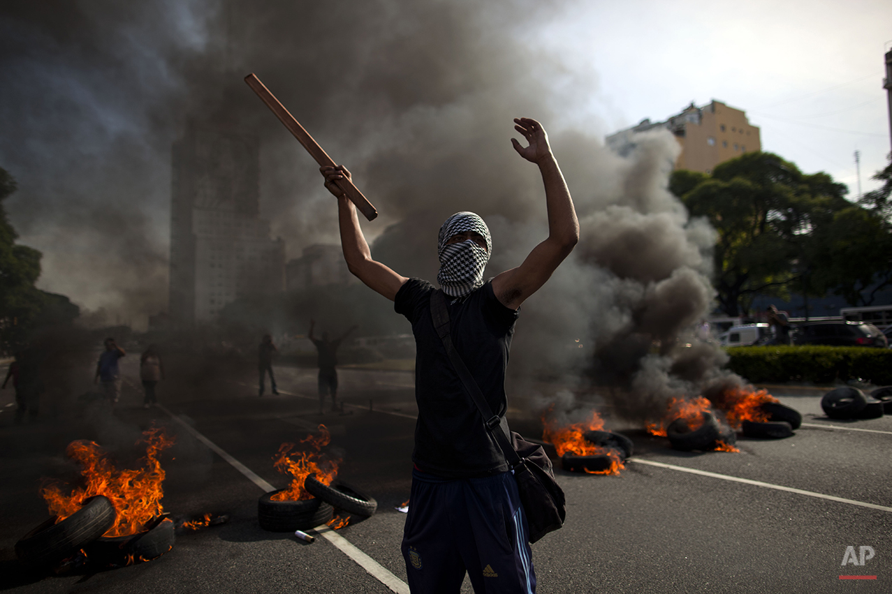 A demonstrator protests in front of tires set on fire in Buenos Aires, Argentina, Tuesday, Dec. 20, 2011. The protest marked the 10th anniversary of the Dec. 20, 2001, financial meltdown that forced a searing devaluation and then-President Fernando de la Rua's resignation. (AP Photo/Natacha Pisarenko)