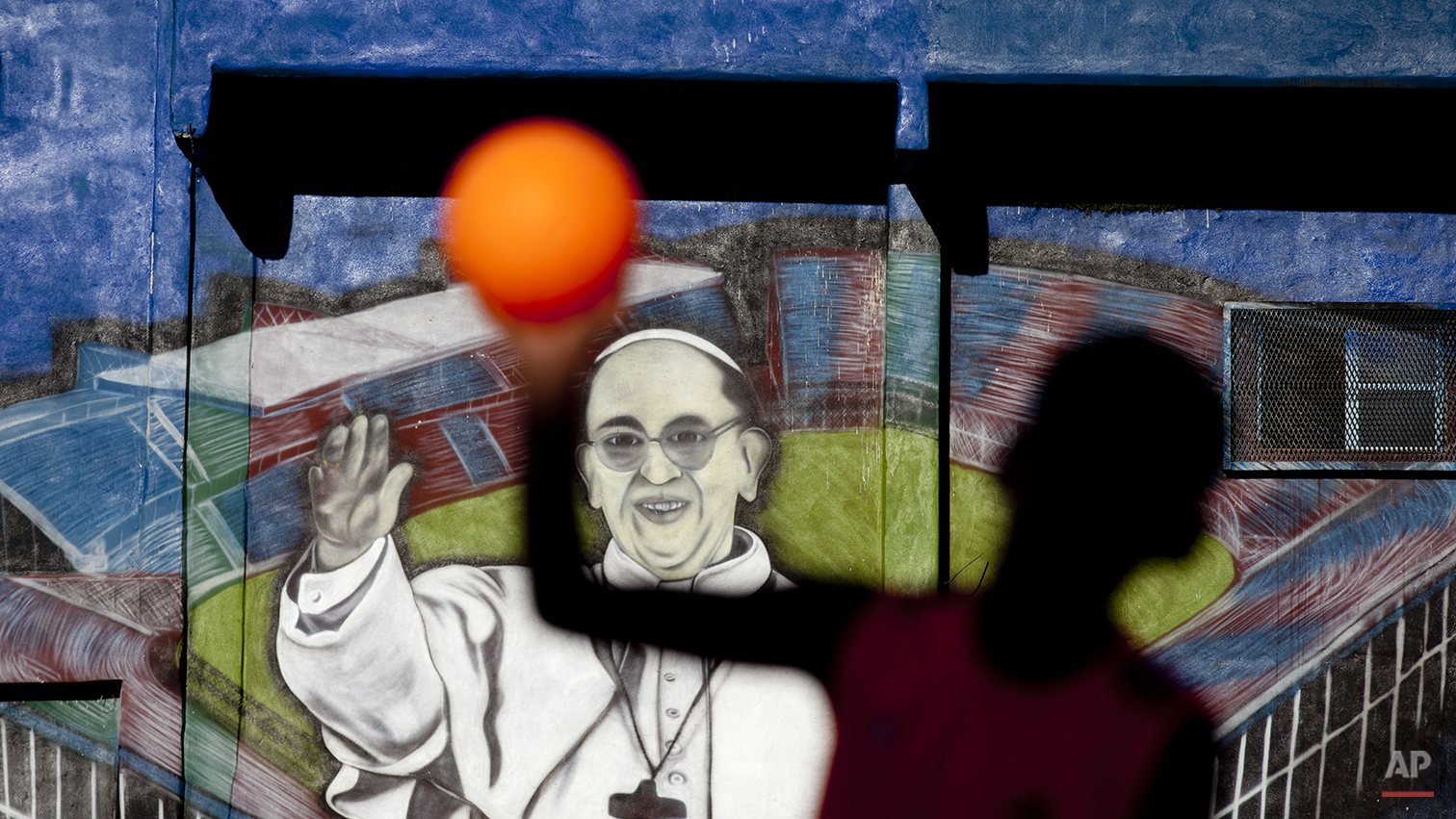 A child plays soccer in front a mural of Pope Francis at the 1-11-14 slum in Buenos Aires, Argentina, Thursday, March 13, 2014. On the day of the first anniversary of the Pope's election, people from the 1-11-14 slum gather at the their church to attend a mass given in his honor and to watch an interview that Pope Francis gave recently from his residence at the Vatican to FM Bajo Flores, a community radio station that broadcasts from the slum. (AP Photo/Natacha Pisarenko)