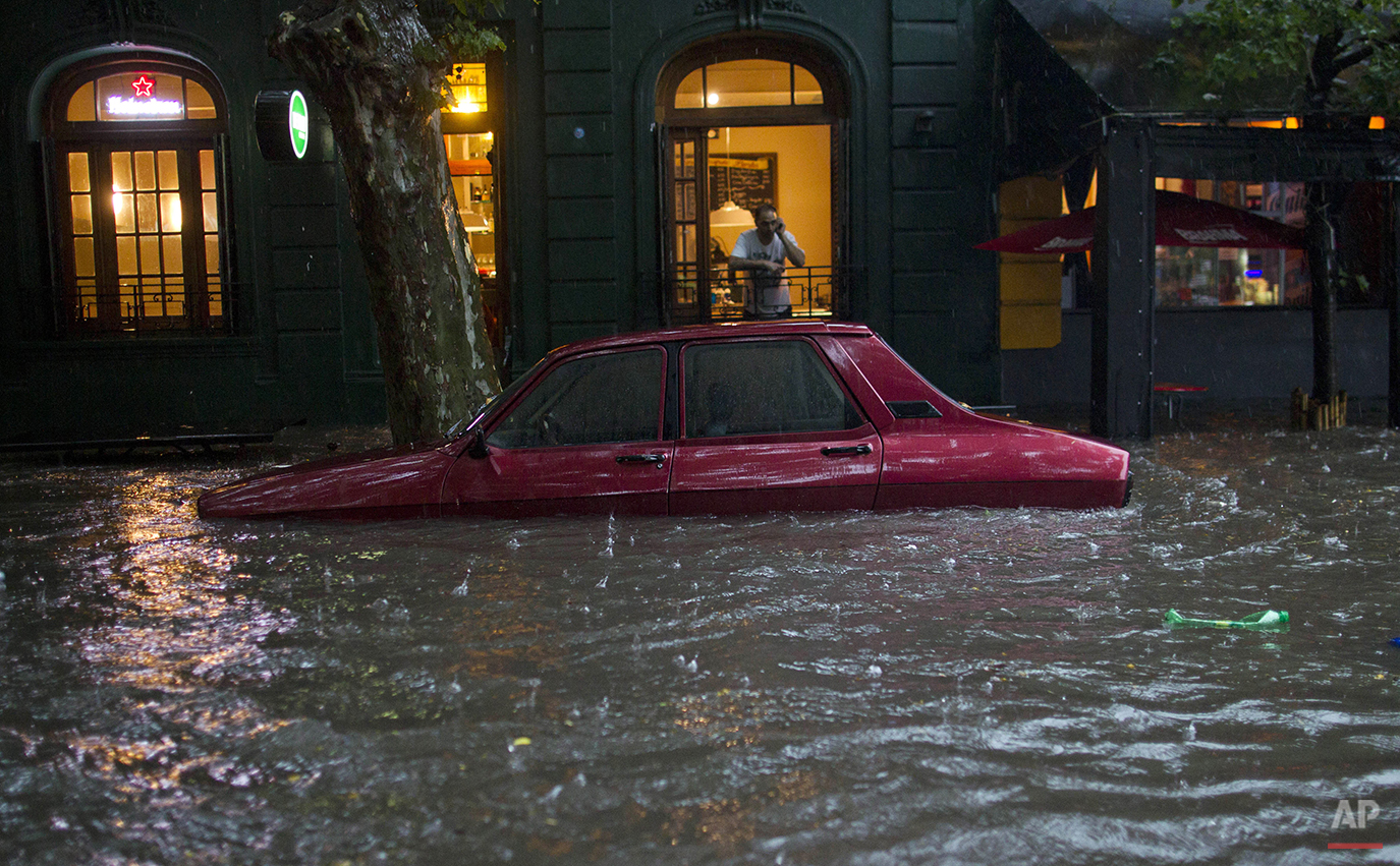 A car is submerged in flood water in front of a home in Buenos Aires, Argentina, Thursday, Dec. 6, 2012.  Heavy rain flooded the capital on Thursday. (AP Photo/Natacha Pisarenko)