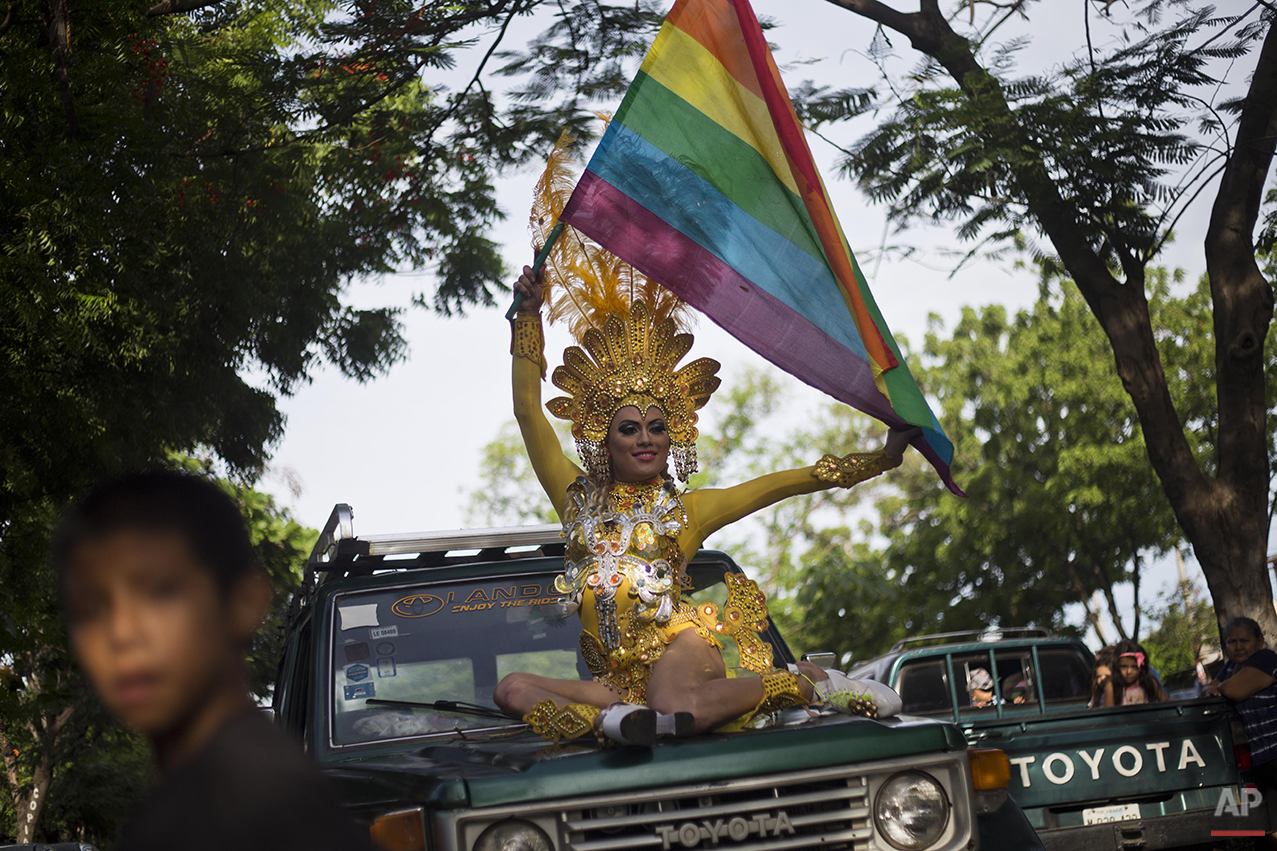 A reveler holds a gay pride flag during a parade celebration in Managua, Nicaragua, Sunday, June 28, 2015. (AP Photo/Esteban Felix)