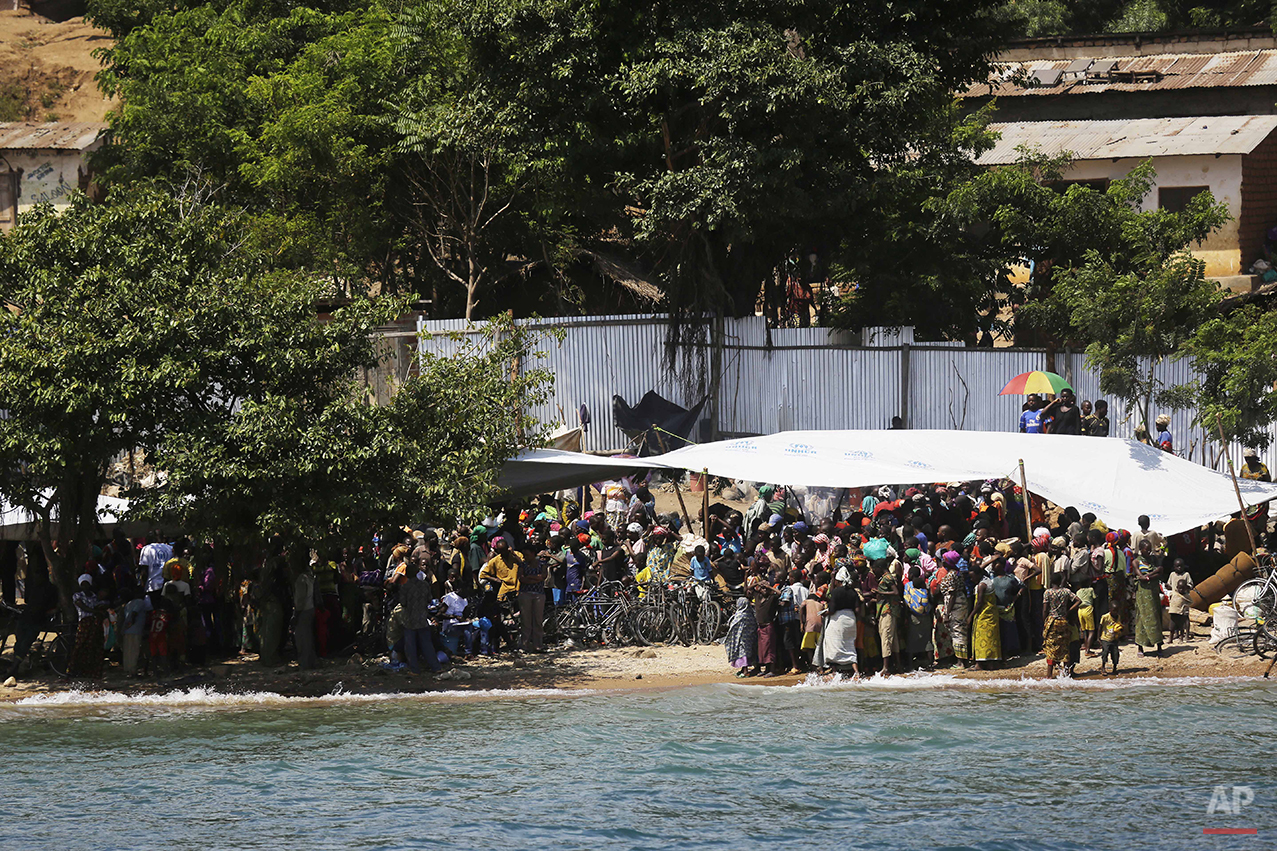Refugees who fled Burundi's violence and political tension watch others  leave on a ship freighted by the UN , at Kagunga on Lake Tanganyika, Tanzania, Saturday, May 23, 2015 to be taken to the port city of Kigoma. An outbreak of cholera has infected 3,000 people in a Tanzanian border region where refugees fleeing political unrest in Burundi have massed, the U.N. Refugee Agency said Friday, May 22, 2015. Some 300 to 400 new cases of cholera are being reported daily. At least 31 people — 29 refugees and two Tanzanians — already have died of the disease, according to UNHCR. More than 64,000 Burundians have fled to Tanzania in recent weeks, UNHCR said, escaping the unrest sparked by their president's bid for a third term that many say is unconstitutional. (AP Photo/Jerome Delay)