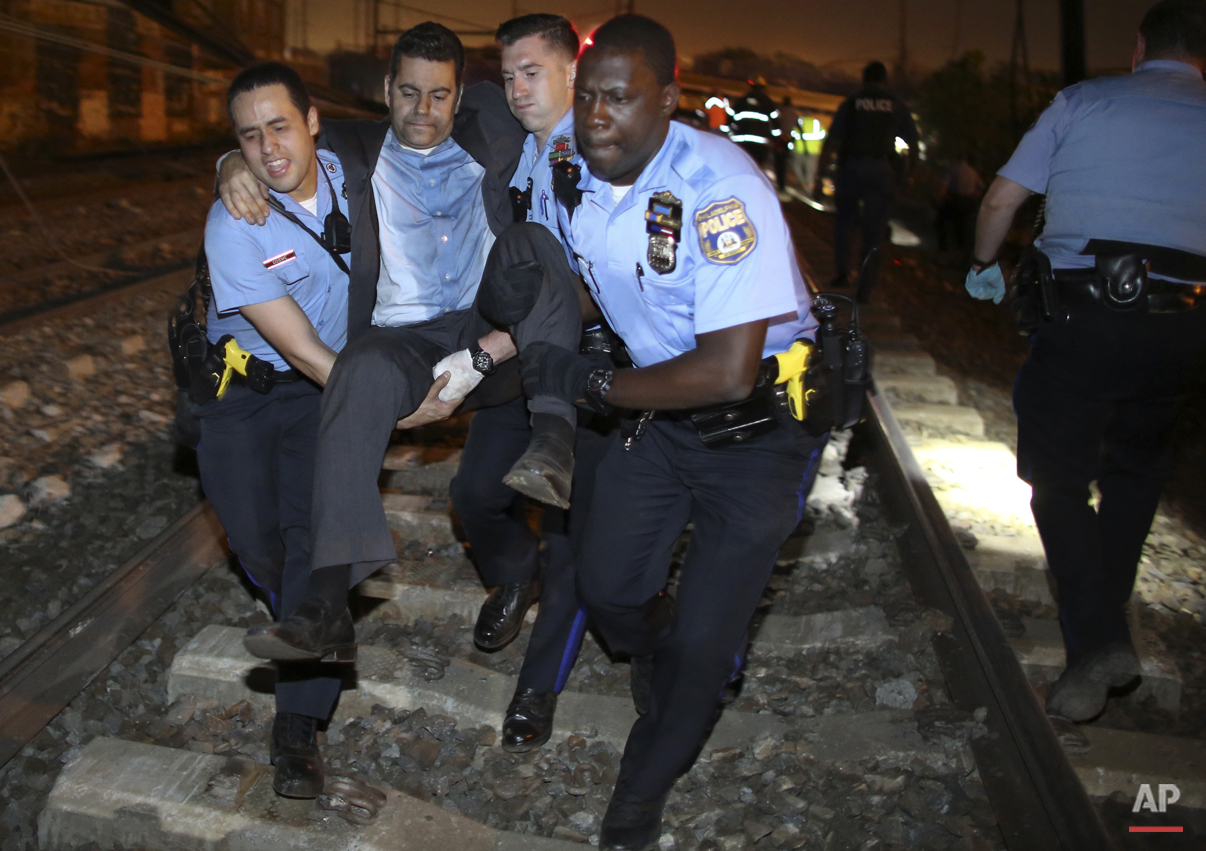 Emergency personnel help a passenger at the scene of a Amtrak train wreck, Tuesday, May 12, 2015, in Philadelphia. (AP Photo/Joseph Kaczmarek)