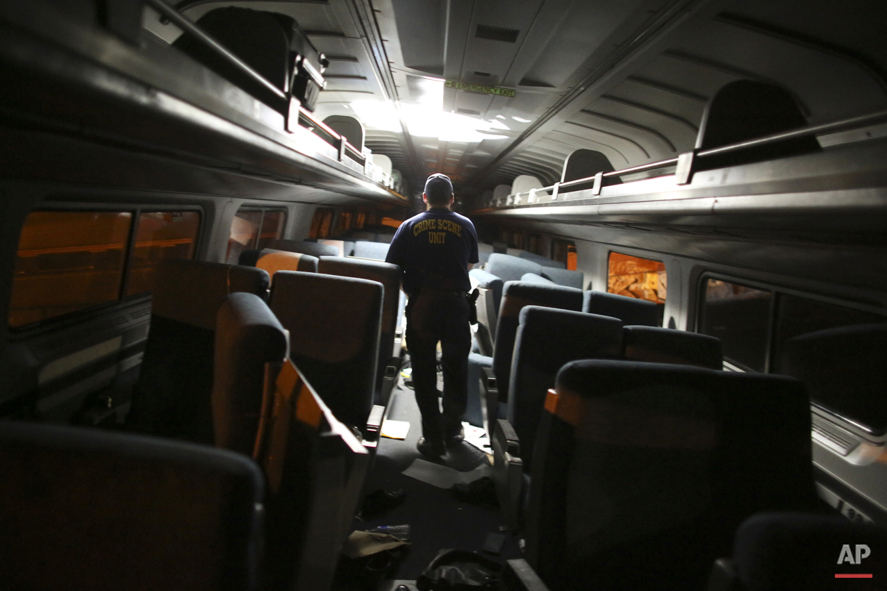 A crime scene investigator looks inside a train car after a Amtrak train wreck, Tuesday, May 12, 2015, in Philadelphia. (AP Photo/Joseph Kaczmarek)