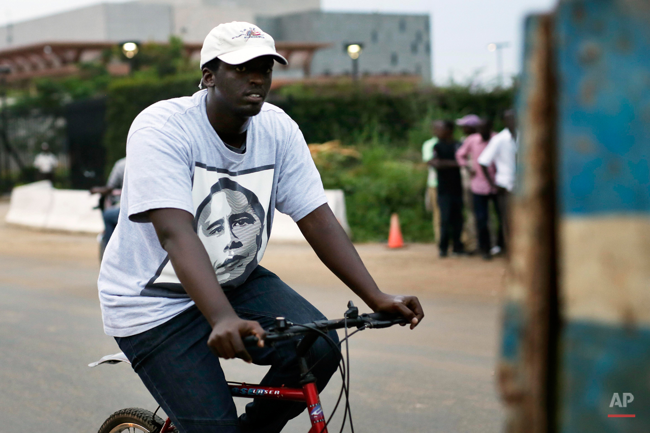 In this photo taken Saturday May 30, 2015, a man rides his bicycle wearing a T-shirt with the portrait of U.S. President Barak Obama in Bujumbura, Burundi. Barack Obama, the United Statesí first African-American president, has captured the imagination of people across the continent where his face shows up on billboards, backpacks, T-shirts and restaurants.  On Friday, July 24, 2015 Obama will be visiting Kenya, where his father was born, for a summit on entrepreneurship before heading to Ethiopia to address leaders at the African Union headquarters. Wherever he goes, large crowds are expected to gather and cheer him.(AP Photo/Jerome Delay)