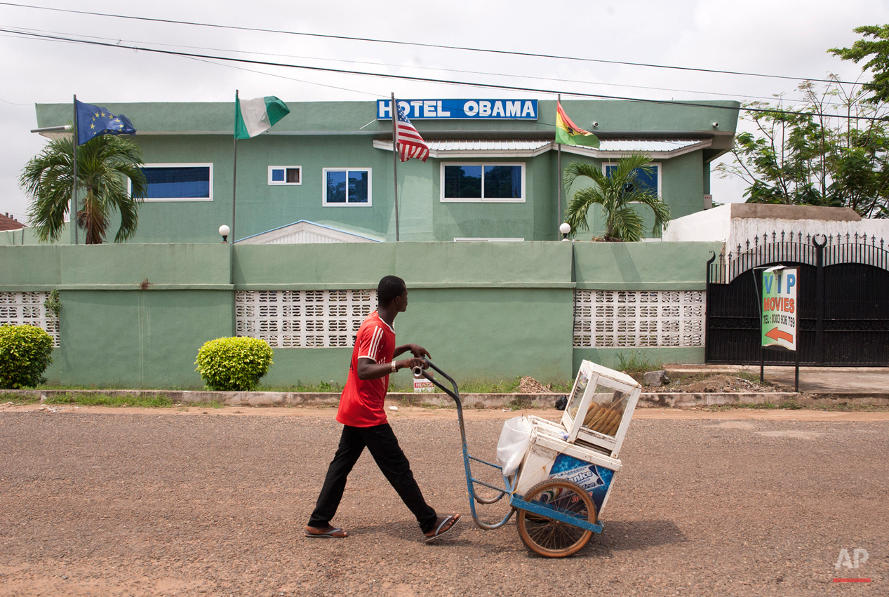 In this picture taken on Saturday, July 4, 2015, an ice cream vendor walks by a hotel named after U.S. President Barak Obama in Accra, Ghana. Barack Obama, the United Statesí first African-American president, has captured the imagination of people across the continent where his face shows up on billboards, backpacks, T-shirts and restaurants.  On Friday, July 24, 2015 Obama will be visiting Kenya, where his father was born, for a summit on entrepreneurship before heading to Ethiopia to address leaders at the African Union headquarters. Wherever he goes, large crowds are expected to gather and cheer him.(AP Photo/Christian Thompson)