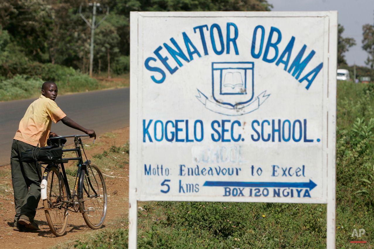 In this Tuesday, Feb. 5, 2008 photo, a boy pushes his bicycle past a sign for the Senator Obama secondary school in the village of Kogelo, Kenya where Barack Obama's grandmother lives. Barack Obama, the United Statesí first African-American president, has captured the imagination of people across the continent where his face shows up on billboards, backpacks, T-shirts and restaurants. On Friday, July 24, 2015 Obama will be visiting Kenya, where his father was born, for a summit on entrepreneurship before heading to Ethiopia to address leaders at the African Union headquarters. Wherever he goes, large crowds are expected to gather and cheer him.(AP Photo/Ben Curtis)