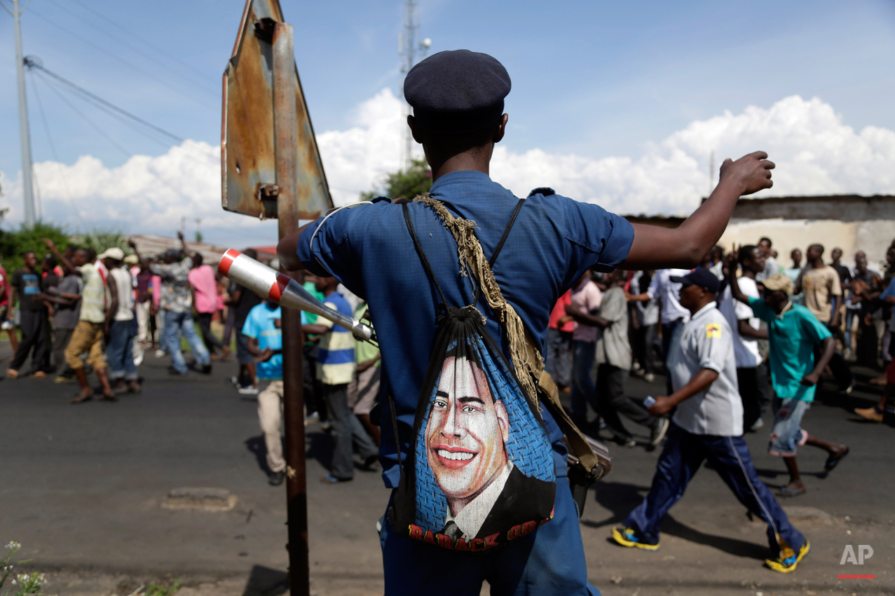 In this photo taken Monday May 11, 2015, a police officer keeping watch on demonstrators in Bujumbura, Burundi, carries a bag with the portrait of U.S. President Barak Obama. Barack Obama, the United Statesí first African-American president, has captured the imagination of people across the continent where his face shows up on billboards, backpacks, T-shirts and restaurants.  On Friday, July 24, 2015 Obama will be visiting Kenya, where his father was born, for a summit on entrepreneurship before heading to Ethiopia to address leaders at the African Union headquarters. Wherever he goes, large crowds are expected to gather and cheer him. (AP Photo/Jerome Delay)