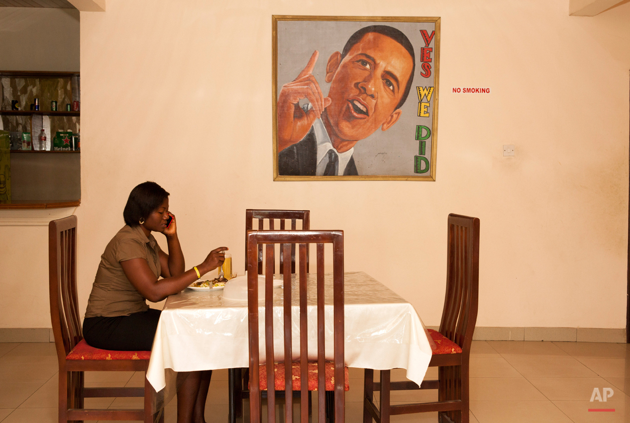 In this picture taken on Saturday, July 4, 2015, a woman sits in the restaurant of  a hotel named after U.S. President Barak Obama in Accra, Ghana. Barack Obama, the United Statesí first African-American president, has captured the imagination of people across the continent where his face shows up on billboards, backpacks, T-shirts and restaurants.  On Friday, July 24, 2015 Obama will be visiting Kenya, where his father was born, for a summit on entrepreneurship before heading to Ethiopia to address leaders at the African Union headquarters. Wherever he goes, large crowds are expected to gather and cheer him.(AP Photo/Christian Thompson)