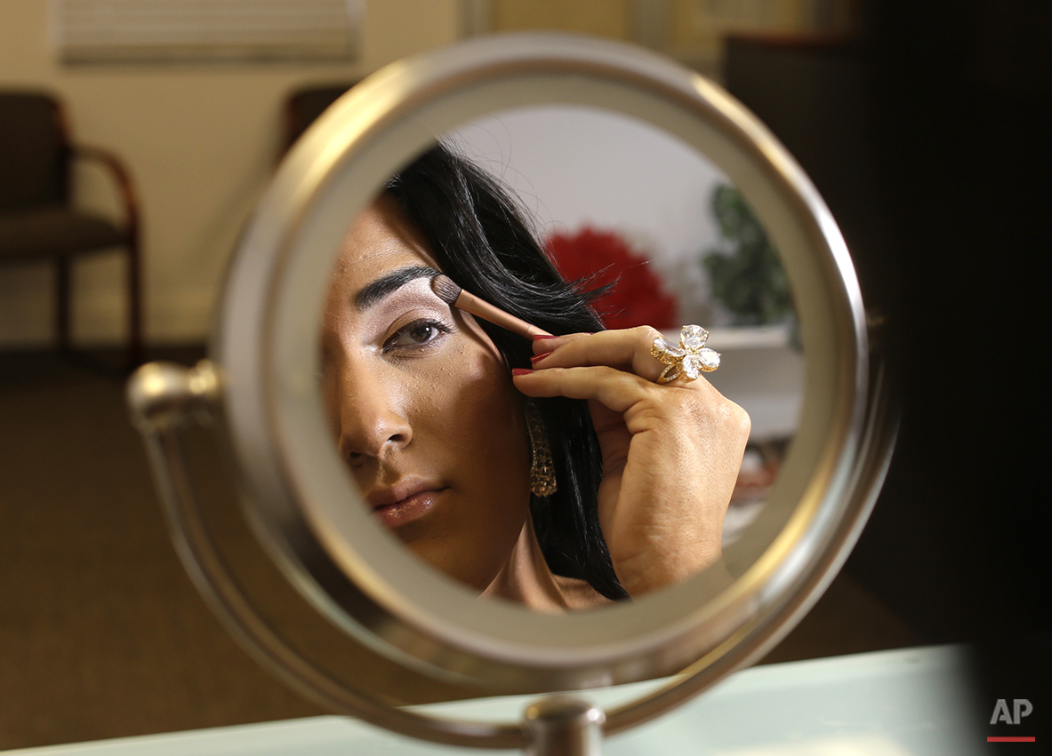 In this photo taken June 6, 2015, Andii Viveros, 21, of Davie, Fla., applies makeup as she prepares to host the annual Sun Serve LGBTQA Colors of the Wind youth prom in Fort Lauderdale, Fla. Viveros, who identifies as a transgender female, said she was always different from an early age growing up as a boy. Her parents accepted her to be any way she wanted to be. She fought for her rights in high school, sometimes violating the school's code of conduct by wearing dresses. She was elected prom queen in high school and is now studying sociology in college. (AP Photo/Lynne Sladky)
