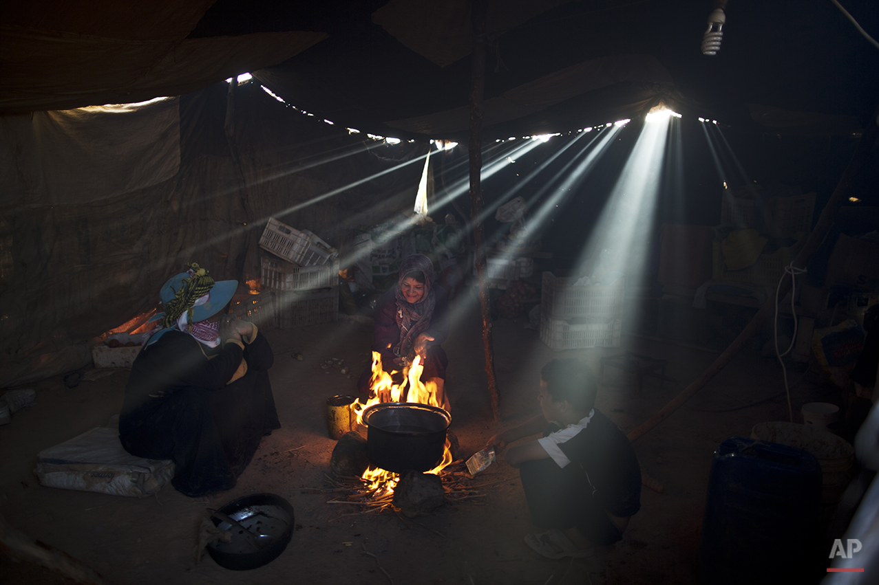 In this Sunday, July 26, 2015 photo, a Syrian refugee girl sits with her mother while cooking on a fire inside their tent at an informal tented settlement near the Syrian border on the outskirts of Mafraq, Jordan. Most of those in Mafraq choose to live here to be able to work at nearby farms, chaffing at the restrictions put on them in formal, U.N.-administered refugee camps. But even those salaries are not enough to support them. (AP Photo/Muhammed Muheisen)