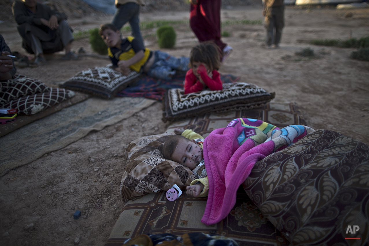 In this Sunday, July 19, 2015 photo, Syrian refugee child, 4-month-old Marwa al-Hassan, her face covered with flies, sleeps on the ground outside her family's tent to avoid the heat trapped inside, at an informal tented settlement near the Syrian border on the outskirts of Mafraq, Jordan. Of the 4 million refugees who fled Syria's grinding civil war, it is the conflict's youngest exiles who often bear the brunt of its woes. (AP Photo/Muhammed Muheisen)