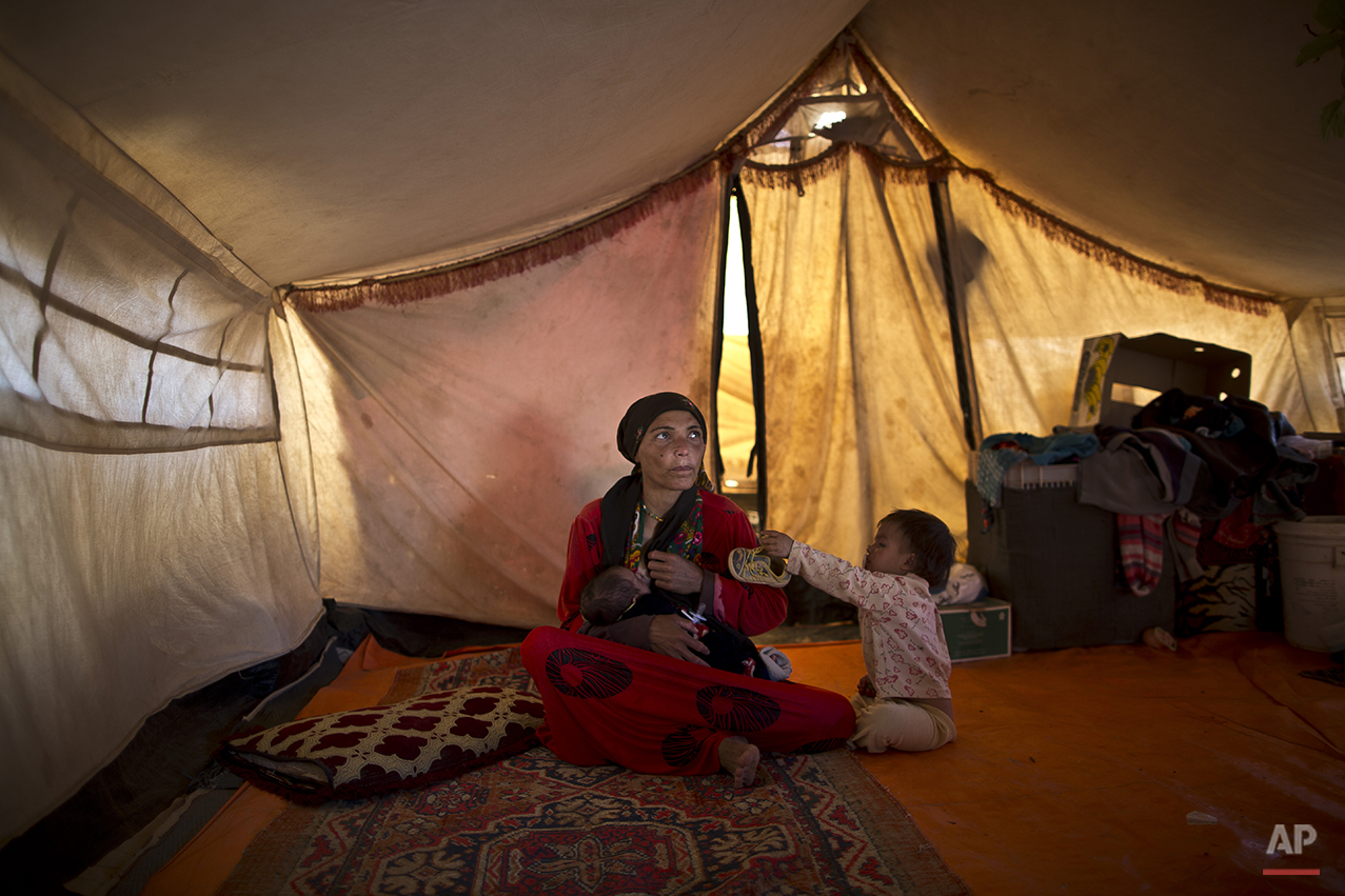 In this Sunday, July 26, 2015 photo, Syrian refugee Wazeera Elaiwi, 29, breast-feeds her newly born son Mohammed, 43 days, inside her tent at an informal settlement near the Syrian border on the outskirts of Mafraq, Jordan. Aid agencies asked for $4.5 billion for 2015 to help refugees, but have been forced to slash support programs because of large funding gaps. That's had a devastating effect on the amount of food aid coming. (AP Photo/Muhammed Muheisen)