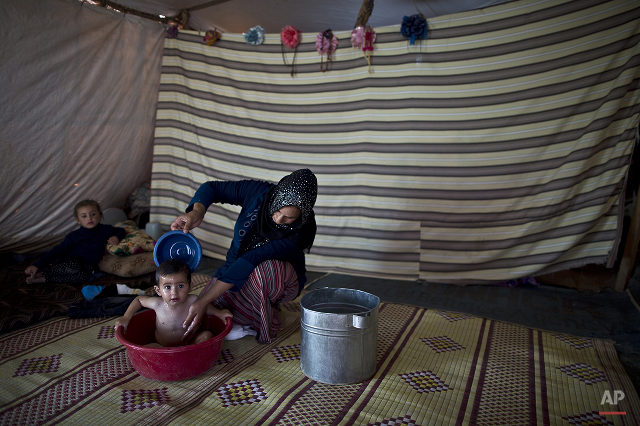 In this Saturday, July 25, 2015 photo, Syrian refugee Joriya Hatem, 20, bathes her son Mahmoud, 1, in a bucket inside their tent at an informal tented settlement near the Syrian border on the outskirts of Mafraq, Jordan. Of the 4 million refugees who fled Syria's grinding civil war, it is the conflict's youngest exiles who often bear the brunt of its woes. (AP Photo/Muhammed Muheisen)