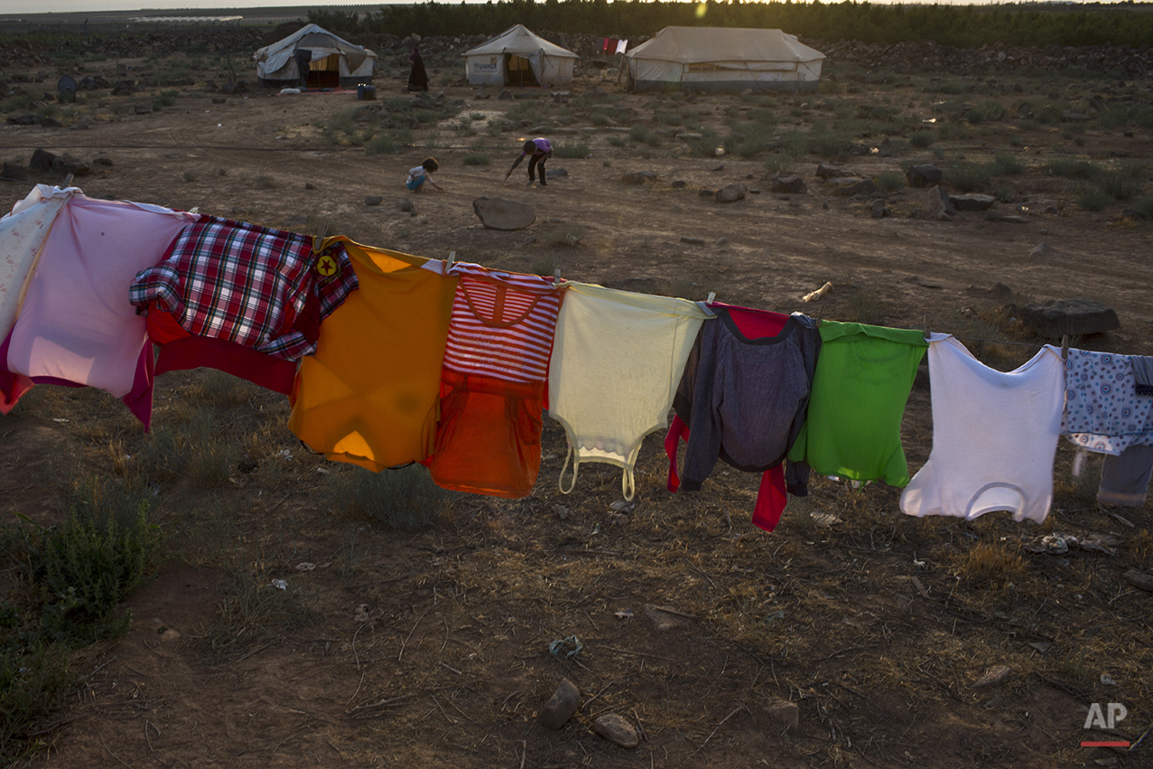 In this Monday, July 27, 2015 photo, clothes of Syrian refugee children hang out to dry outside a tent at an informal settlement near the Syrian border on the outskirts of Mafraq, Jordan. More than 10,000 children have died in Syria's four-year conflict, while over 2.8 million in and out of the country don't go to school, according to the U.N. children's agency, UNICEF. (AP Photo/Muhammed Muheisen)