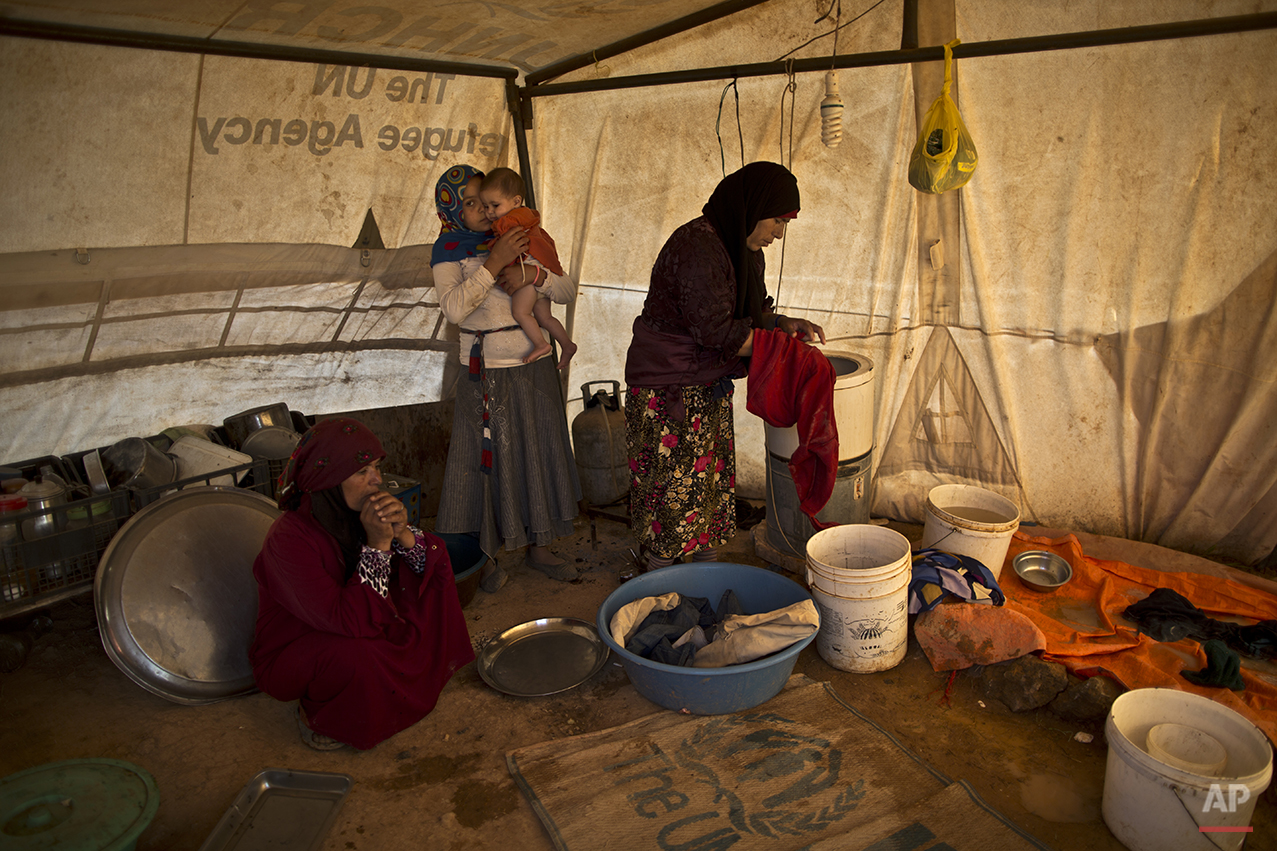 In this Wednesday, July 22, 2015 photo, a Syrian refugee girl holds her younger sister while her mother, right, washes clothes inside their tent at an informal settlement near the Syrian border on the outskirts of Mafraq, Jordan. Aid agencies asked for $4.5 billion for 2015 to help refugees, but have been forced to slash support programs because of large funding gaps. That's had a devastating effect on the amount of food aid coming. (AP Photo/Muhammed Muheisen)