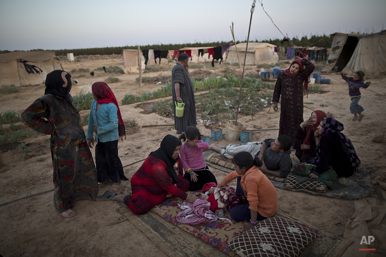 In this Sunday, July 26, 2015 photo, a Syrian refugee woman sits on the ground next to her infant suffering from a high temperature due to an infection in her throat, outside their tent at an informal settlement near the Syrian border on the outskirts of Mafraq, Jordan. Most of those in Mafraq choose to live here to be able to work at nearby farms, chaffing at the restrictions put on them in formal, U.N.-administered refugee camps. But even those salaries are not enough to support them. (AP Photo/Muhammed Muheisen)