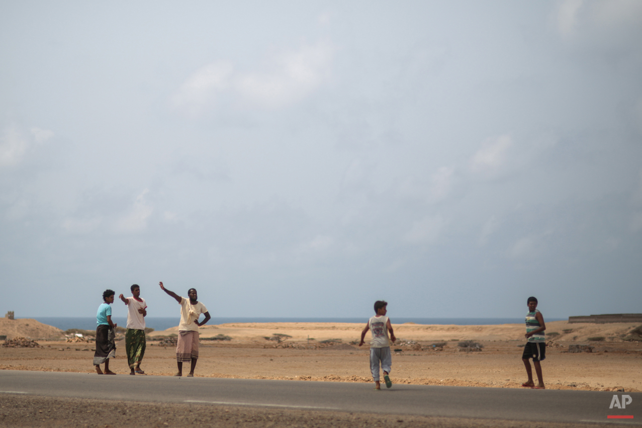 In this Wednesday, May 20, 2015 photo, Yemeni refugees gesture trying to hitchhike a ride from their camp to the center of Obock city, to the nearest shop, northern Djibouti. The UNHCR says a total of 5,000 Yemeni refugees have made it to Djibouti, including 3,000 in the capital, Djibouti city, and 1,000 in Obock, 300 kilometers (187 miles) to the north making it currently the biggest Yemeni refugee population. (AP Photo/Mosa'ab Elshamy)