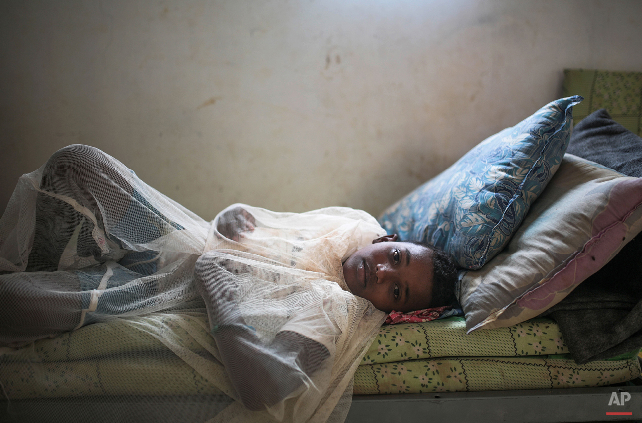 In this Tuesday, May 19, 2015 photo, Abo Bakr Mohammed, 12, who suffers from epilepsy, covers himself with a mosquito net in his family's room, at an orphanage that has been turned into a center for Yemeni refugees, in Obock, northern Djibouti. The UNHCR says a total of 5,000 Yemeni refugees have made it to Djibouti, including 3,000 in the capital, Djibouti city, and 1,000 in Obock, 300 kilometers (187 miles) to the north making it currently the biggest Yemeni refugee population. (AP Photo/Mosa'ab Elshamy)