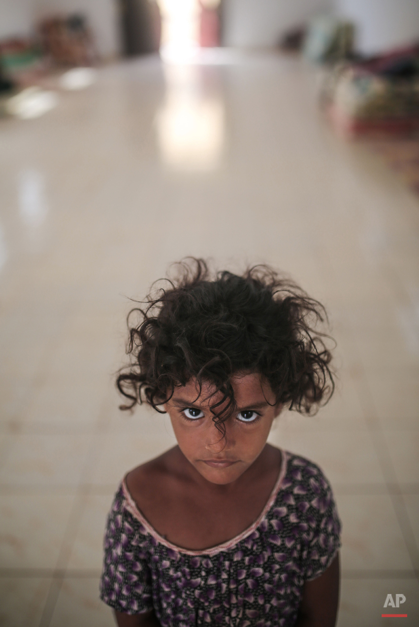 In this Wednesday, May 20, 2015 photo, Aseya, 3, poses for a photo in her family's room in at an orphanage that has been turned into a center for Yemeni refugees, in Obock, northern Djibouti. Fleeing the war at home, thousands of Yemenis have made it across the Gulf of Aden to find refuge in Djibouti, a sleepy Horn of Africa nation where the United Nations has set up a staging hub for aid for the conflict-torn Arab country. (AP Photo/Mosa'ab Elshamy)