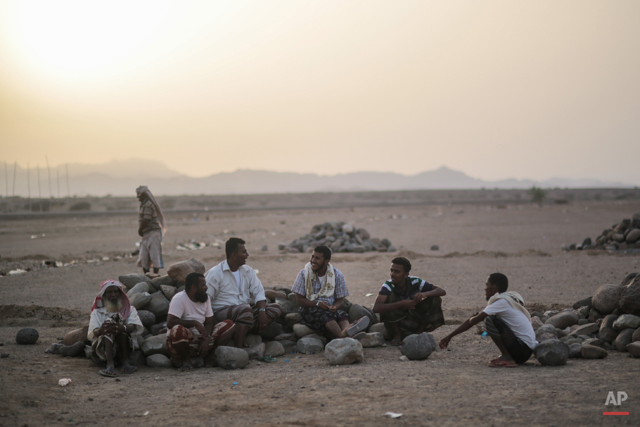 In this Wednesday, May 20, 2015 photo, Yemeni refugees chat at the end of the day outside the Markaze refugee camp where Yemeni refugees are stationed, in Obock, northern Djibouti. Many of the refugees arrived with just the few belongings they could carry, mostly on small rickety fishing boats, others on bigger vessels crammed with people, reversing a centuries-old perilous route that has seen countless African migrants take to the seas in the other direction. (AP Photo/Mosa'ab Elshamy)