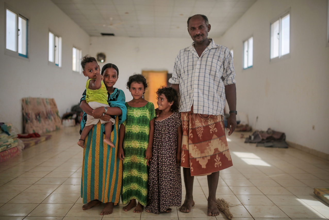 In this Wednesday, May 20, 2015 photo, Ibrahim Omar, 45, right, and his children, Aseya, 3, Heyam, 6, Maryam, 10, and 1-year-old Saeed, pose for a photo as they stand next to their father in their room, at an orphanage that has been turned into a center for Yemeni refugees, in Obock, northern Djibouti. In Obock, the Al-Rahma orphanage has become home to about 100 families, mostly from the Yemeni town of Bab Al-Mandab just a 30-minute boat trip from Obock. (AP Photo/Mosa'ab Elshamy)