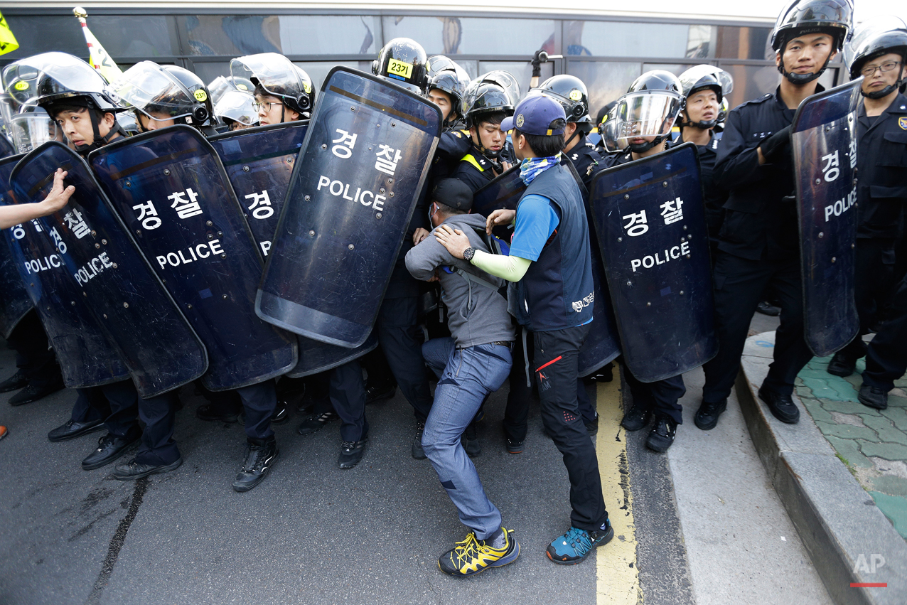 Members of the Korean Confederation of Trade Unions confront with riot police as they march toward the presidential house after a May Day rally in Seoul, South Korea, Friday, May 1, 2015. Thousands of South Koreans marched in Seoul on Friday for a third week to protest government labor policies and the handling of a ferry disaster that killed more than 300 people a year ago.(AP Photo/Ahn Young-joon)