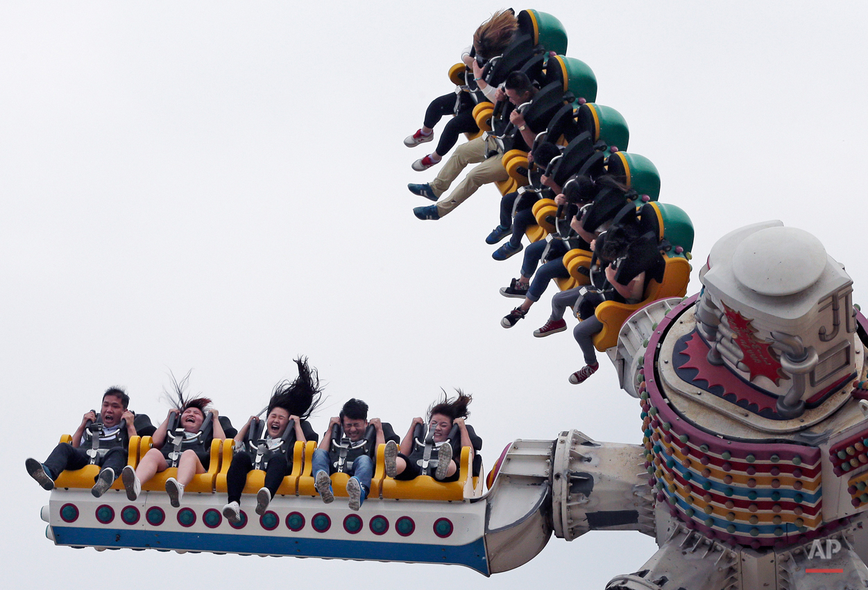 People react on an a ride at Xiedao's theme park during a May Day holiday in Beijing, China, Friday, May 1, 2015. Millions of Chinese are taking advantage of the May Day holidays to visit popular tourist sites. (AP Photo/Andy Wong)
