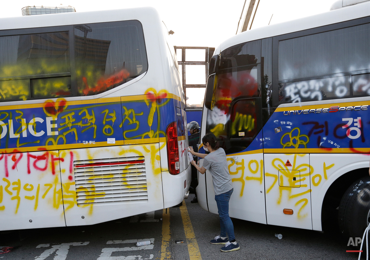 A member of the Korean Confederation of Trade Unions sprays paints to write a message denouncing South Korean President Park Geun-hye on police buses after a May Day rally in Seoul, South Korea, Friday, May 1, 2015. Thousands of South Koreans marched in Seoul on Friday for a third week to protest government labor policies and the handling of a ferry disaster that killed more than 300 people a year ago. (AP Photo/Ahn Young-joon)