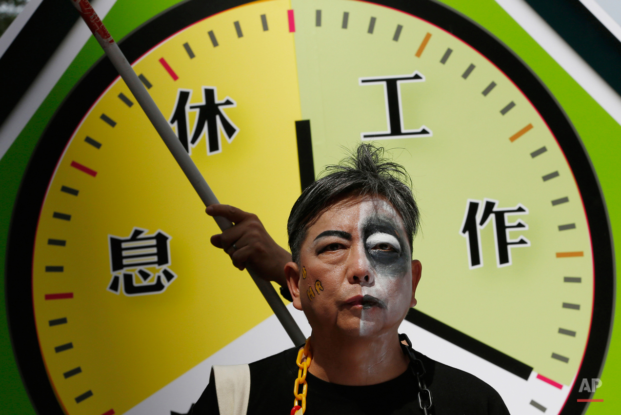 "A protester with half of his face painted as zombie in front of a mock clock divided into ""rest,"" left, and ""work,"" right, during a march to mark May Day in Hong Kong Friday, May 1, 2015. Hundreds of protesters from various labor unions staged a rally to demand better workers' rights and call for standard working hours. (AP Photo/Kin Cheung)"
