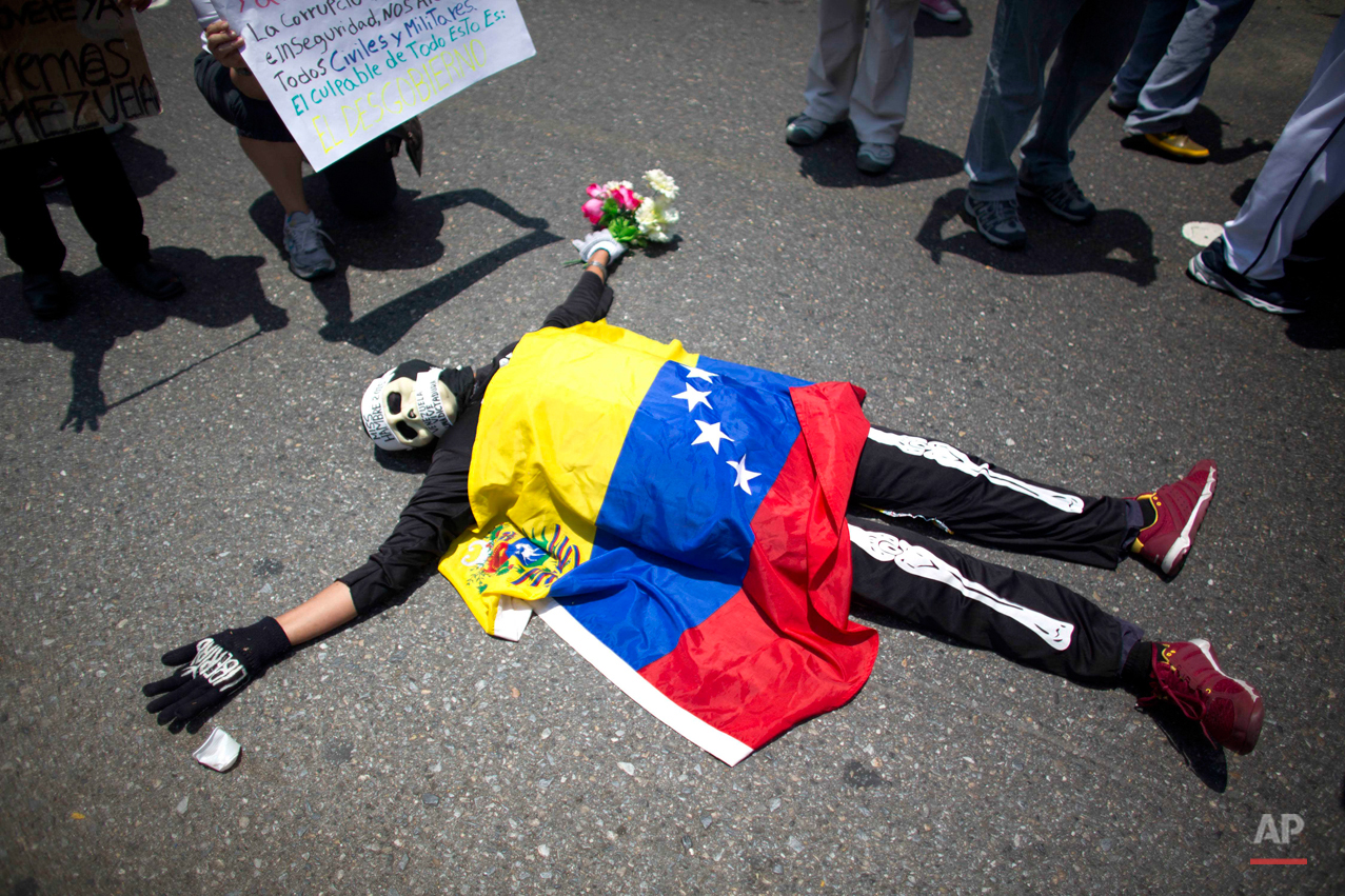 An opposition demonstrator dressed in a skeleton costume with a Venezuelan national flag draped over his body, lies on the pavement, during a May Day march in Caracas, Venezuela, Friday, May 1, 2015. Pro-government and opposition workers marched today in the midst of the political and economic crisis prevailing in the country, with separate marches that took place to mark International Workers Day also known as May Day. (AP Photo/Ariana Cubillos)