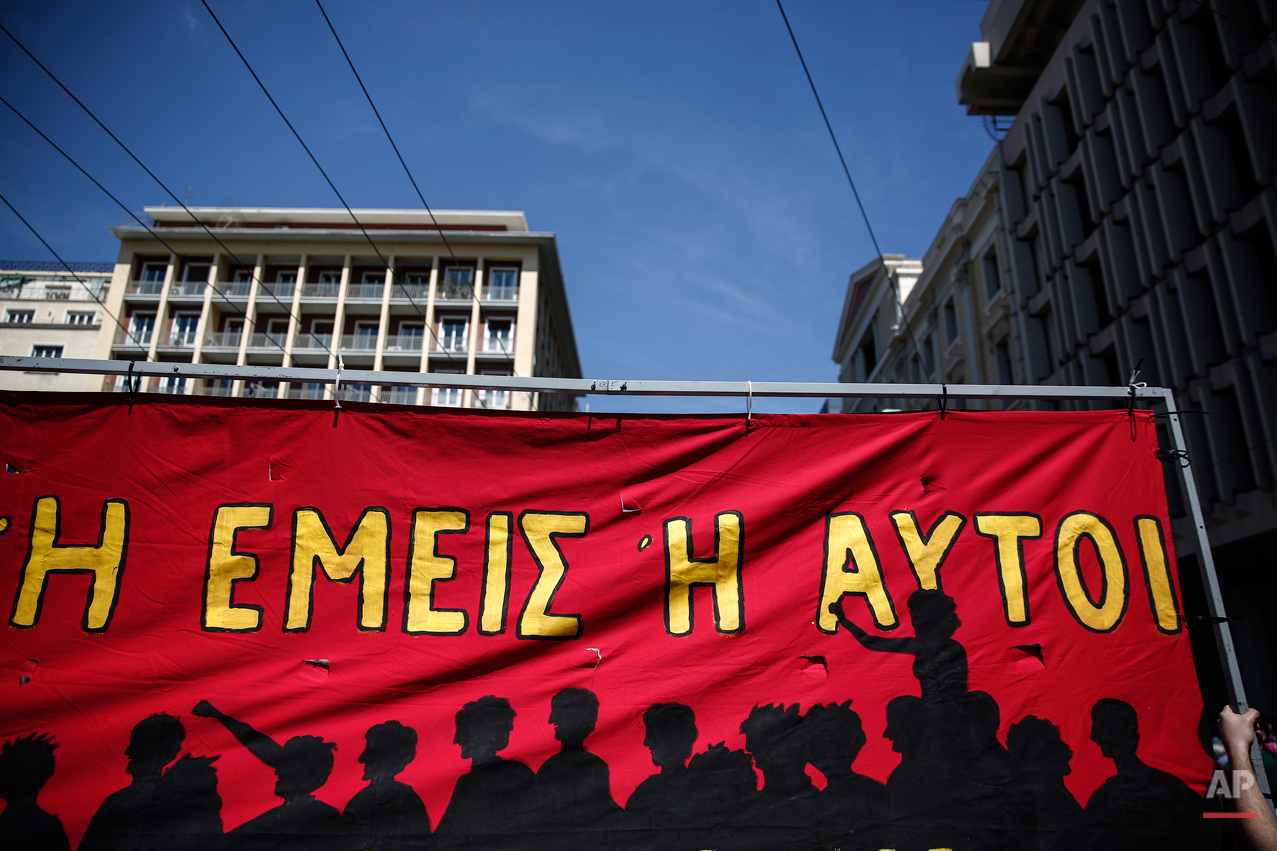 "A protester holds a banner which reads: "" It's either us or them"", during a May Day rally in Athens, Greece, on Friday, May 1, 2015. In financially struggling Greece, an estimated 13,000 people took part in three separate May Day marches in Athens, carrying banners and shouting anti-austerity slogans.   (AP Photo/Yorgos Karahalis)"